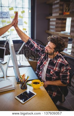 Creative business people high fiving at desk in office