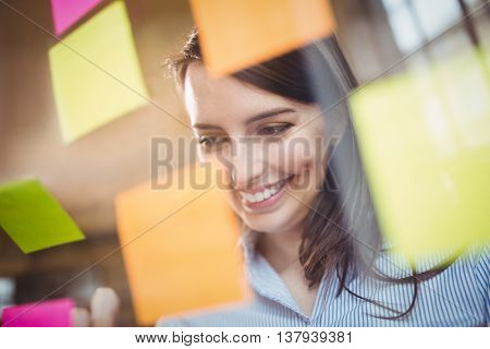 Happy businesswoman looking at sticky notes stuck to glass in creative office