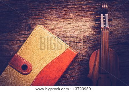 Violin and notebook on grunge dark wood background Vintage style.