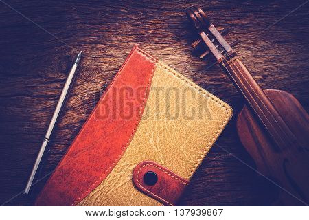 Violin and notebook with pen on grunge dark wood background Vintage style.