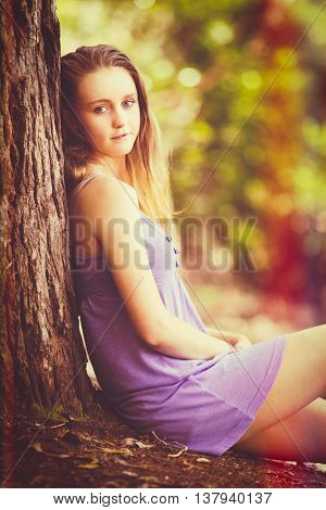 Pretty girl sitting by tree