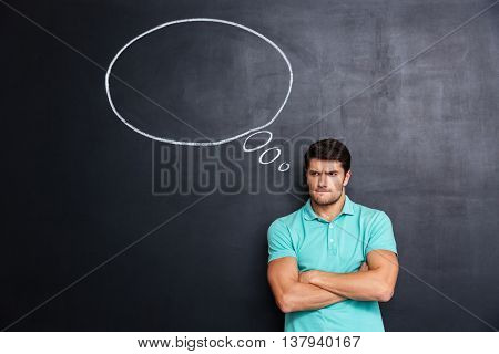 Sad frowning young man standing with hands folded over chalkboard background