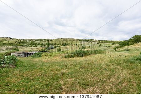 View on moldovan village green hills with sheepfold in summer time