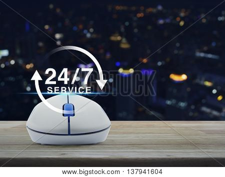 Wireless computer mouse with button 24 hours service icon on wooden table in front of blurred light city tower Full time service concept