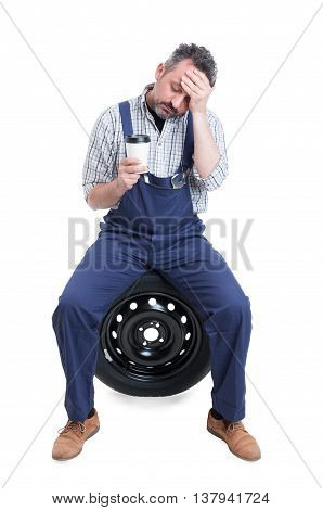 Tired Mechanic Sitting On Tire And Drinking Coffee