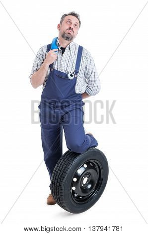 Full Body Of Bored Mechanic Standing Near Wheel