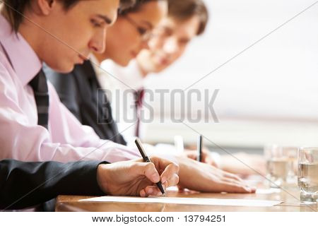 Row of people writing in board room