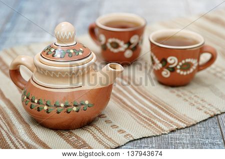 Tea brewed in clay teapot and poured into clay cups made in Ukrainian Transcarpathian (Ruthenian) traditional ornament style, on handmade embroidered traditional towel