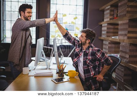 Happy male coworkers high fiving at desk in creative office