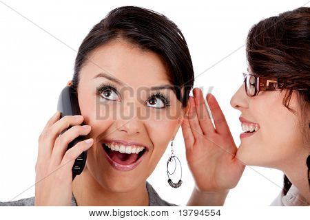 Business woman telling a secret to her co-worker while on the phone