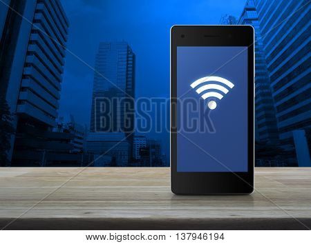Wi-fi connection icon on modern smart phone screen on wooden table over city tower background Technology and internet concept