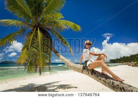 Beautiful woman sitting on a palmtree in La Digue, Seychelles