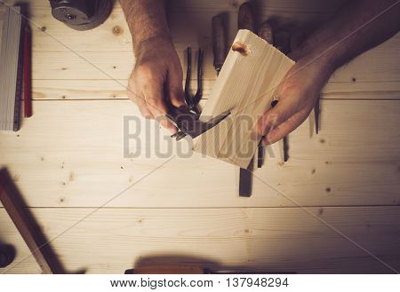 Cropped image of senior carpenter measuring wood in workshop