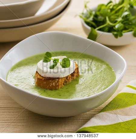 A bowl of watercress soup garnished with toast and goat cheese.