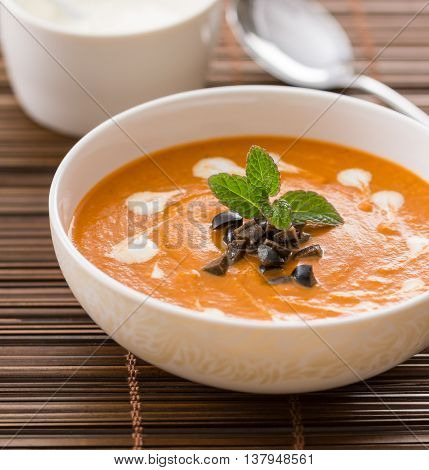 Vegetarian cream soup with eggplant garnished with cream olives and mint
