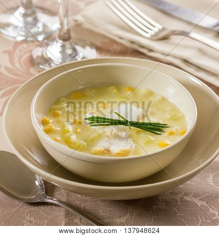 A chowder soup with fish and corn in a bowl