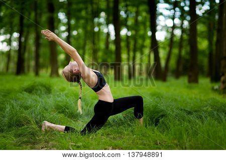 Nature yoga session in beautiful green polish woods between trees. Warrior pose - Virabhadrasana I