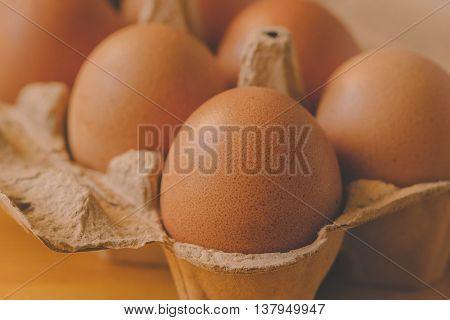 Eggs in cardboard box retro toned selective focus