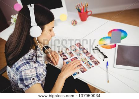 High angle view of woman viewing photographs in creative office
