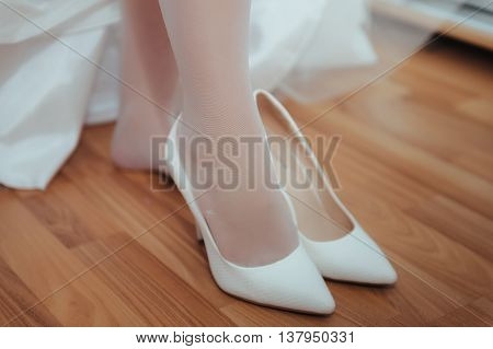 Picture of beautiful female barefoot legs in wedding dress. Bride dresses stockings on feet. Bride putting a wedding garter on her leg