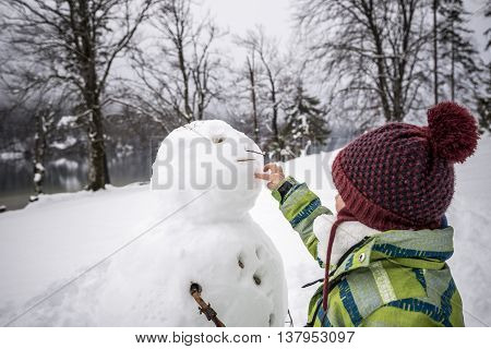 Young child wearing a warm jacket and knitted cap making a winter snowman preparing a hole for the mouth in a snowy landscape.