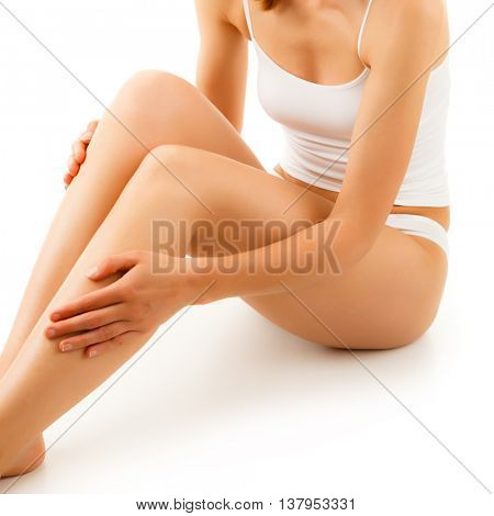 Woman massaging legs sitting on white background