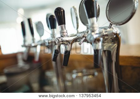 Row of chrome beer taps at cafe