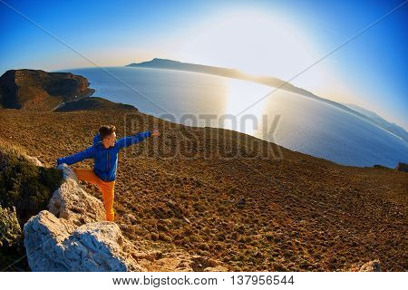 man standing on a cliff against a blue sea and shows at the sea by left hand