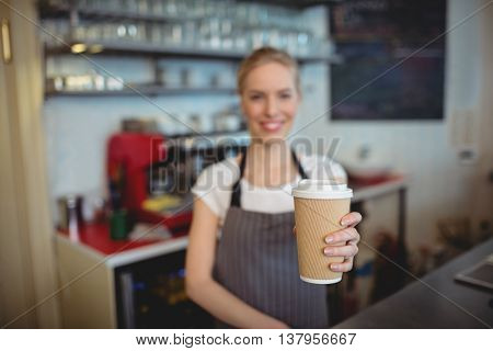 Portrait of female barista holding disposable coffee cup at cafe