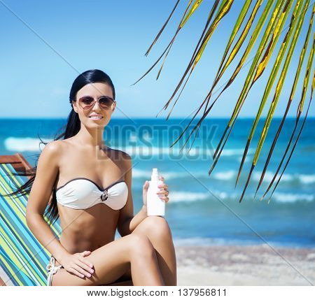 Gorgeous, young, sporty woman wearing sunglasses with a bottle of sunscreen lotion over background with sea and palm.
