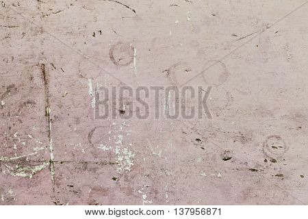 Abstract background of pale pink concrete wall with small cracks and imperfections.