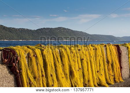 Yellow fishnet drying in the sunlight with blue sky and sea