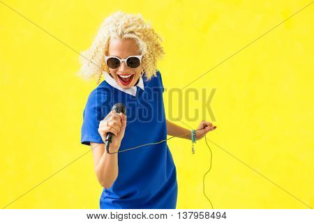 Funny and funky woman singing with microphone