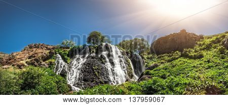 View of beautiful mountain waterfall with blue cloudy sky on background