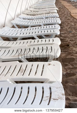 sun beds are placed in a row on the beach in the Crimea