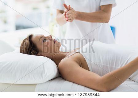Woman receiving reiki treatment at spa