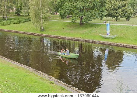 RIGA LATVIA - JUNE 29 2016: Rest on the water - young couple boating at city canal in the historic center of Riga Latvia. Canal was made instead of former fortification walls