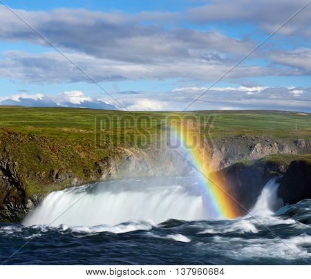 Rainbow near a waterfall. Sunny landscape with a river. Sky with beautiful clouds. Godafoss Waterfall, Iceland, Europe