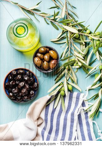 Two bowls with pickled green and black olives, olive tree sprigs and bottle of olive oil on blue Turquoise background, top view, vertical composition