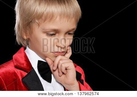 Handsome serious  little boy in a tuxedo on black background