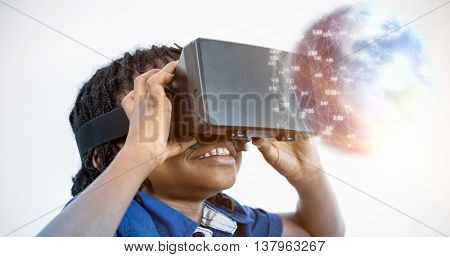 Earth globe against elementary girl looking through virtual reality headset in school library
