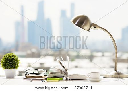 Closeup of workplace with open book stationery items coffee cup glasses decorative plant and table lamp on blurry city background. Education concept