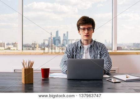 Handsome european man using laptop placed on wooden office desktop with business report coffee cup smartphone and stationery items