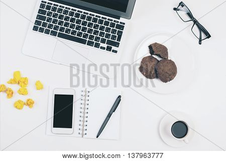 Top view of light office desktop with blank smart phone glasses laptop keyboard coffee cup yellow crumpled paper cookies on plate and other items. Mock up