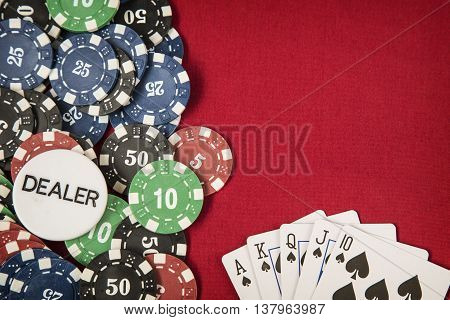 Gambling chips, dealer chip and flush royal on red card table background