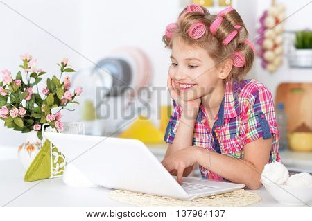 portrait of happy Little pretty girl   in hair curlers   with laptop