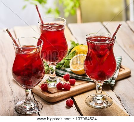 On wooden boards is ice cold beverage glass with red raspberry lemon cocktail . Alcohol country cocktail beverage number ninety eight with mint. Cocktail on outdoor.