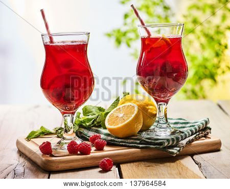 On wooden boards are ice cold beverage two glasses with red berries lemon cocktail . Alcohol country cocktail beverage number ninety seven with leaf mint. Outdoor cocktail .