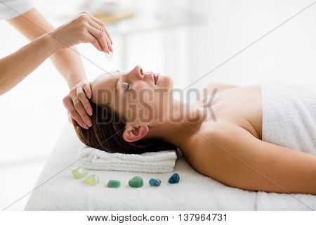 Masseur giving massage treatment to woman at spa