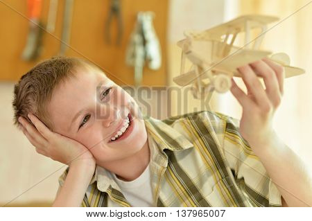 portrait of a boy with a wooden airplane
